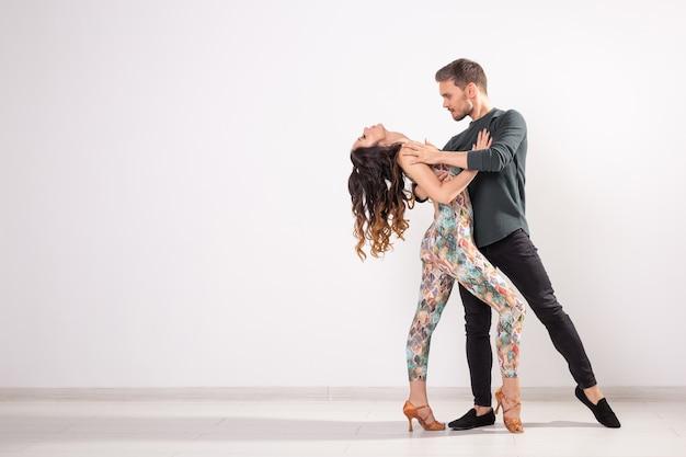 사교 댄스, 바차타, 키좀바, 탱고, 살사, 사람들 개념 - 복사 공간이 있는 흰색 배경 위에 춤을 추는 젊은 부부