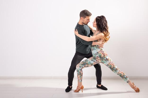 Социальный танец, бачата, кизомба, танго, сальса, концепция людей - молодая пара танцует над белой