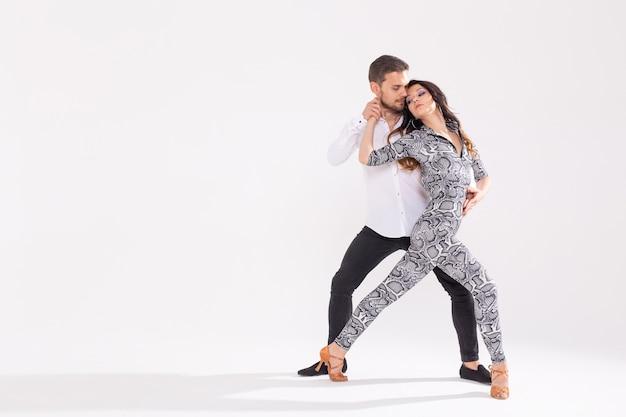 사교 댄스, 바차타, 키좀바, 주크, 탱고 개념 - 남자는 복사 공간이 있는 흰색 배경 위에서 춤을 추면서 여자를 껴안습니다.