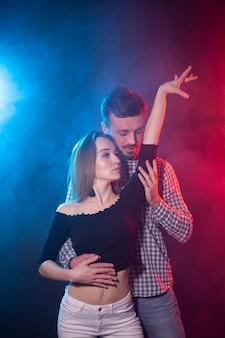 Social dance, bachata, salsa, kizomba, zouk and tango concept - man hugs woman while dancing over lights