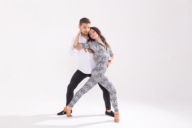 소셜 댄스 개념 - 복사 공간이 있는 흰색 배경 위에 바차타 또는 살사를 함께 춤추는 활동적인 행복한 성인