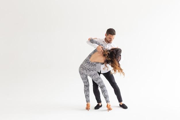 소셜 댄스 개념 - 복사 공간이 있는 흰색 배경 위에 함께 바차타를 춤추는 활동적인 행복한 성인