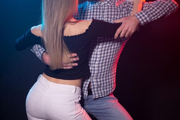 社交ダンスのカップルの人々は夜のクラブでバチャータやサルサを踊る若いカップルをコンセプト