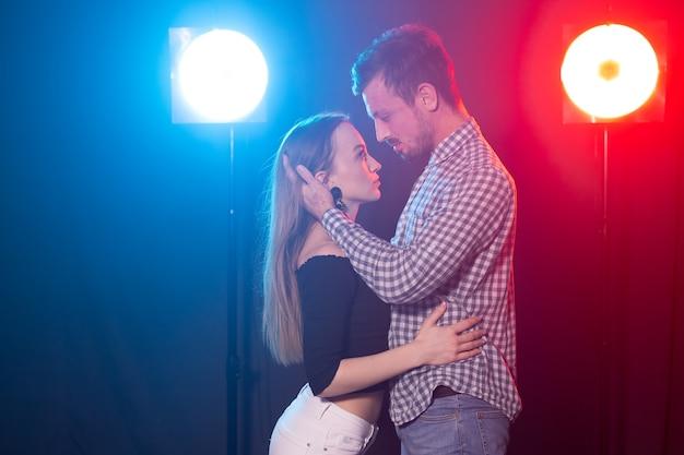 ソシアルダンス、キゾンバ、サルサ、センバのコンセプト-暗闇の中でバチャタやサルサを踊る若い美しいカップル