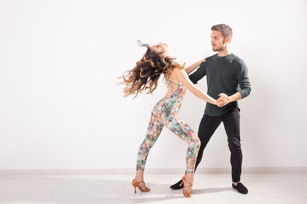 Социальный танец, кизомба, танго, сальса, концепция людей - красивая пара танцует бачату на белом фоне с копией пространства