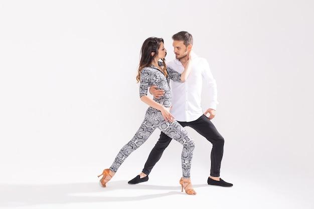 사교 댄스, 키좀바, 탱고, 살사, 사람들 개념 - 복사 공간이 있는 흰색 배경에 바차타 춤을 추는 아름다운 커플