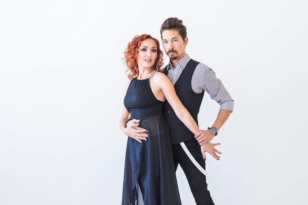 Социальный танец, кизомба, танго, сальса, концепция людей - красивая пара танцует бачату на белой стене с копией пространства
