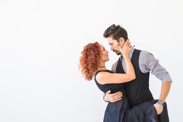ソシアルダンス、サルサ、ズーク、タンゴ、キゾンバのコンセプト-コピースペースのある白い壁の白い壁にバチャタを踊る美しいカップル