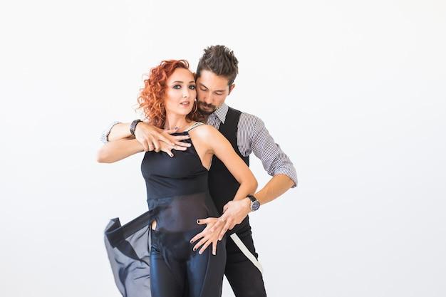 ソシアルダンス、サルサ、ズーク、タンゴ、キゾンバのコンセプト-白でバチャタを踊る美しいカップル