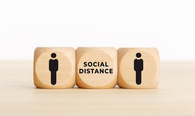 コロナウイルスcovid-19パンデミックに関する社会的距離の概念。人間のアイコンと机の上のテキストと木製のブロック。コピースペース