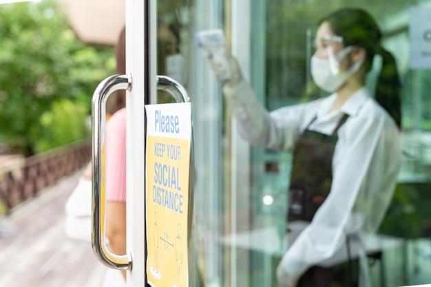 アジアのウェイトレスがお客様の体温を測る、新しい通常のレストランのソーシャルディスタンスサイネージ。新しい通常のレストランのライフスタイルコンセプト。