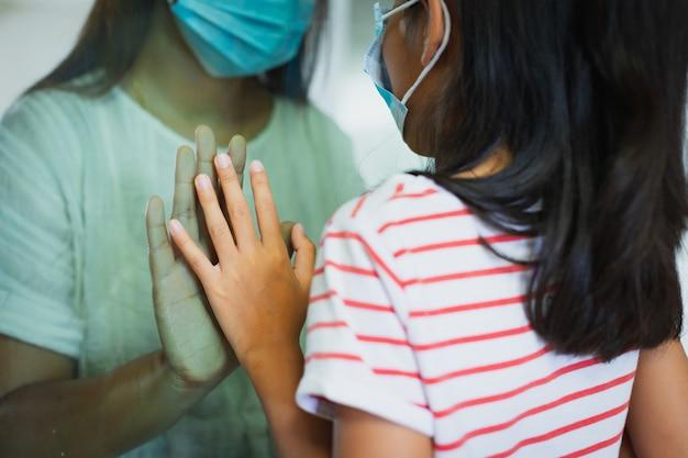 가족 간의 사회적 거리두기. 창 비행기에서 어머니와 딸의 손을 닫습니다. 코로나바이러스 covid-19 전염병으로 인해 격리 기간 동안 집에 있으세요.