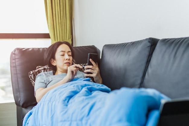 집에서 휴대 전화를 사용하여 소파에 누워 사회적 거리를 두는 아시아 여자