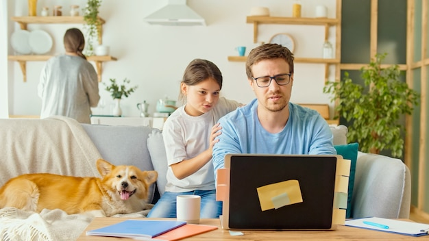 Social distancing. a busy father tries to work remotely with his child and wife at home.