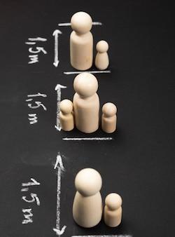 Концепция социального дистанцирования во время пандемии и эпидемий, избегание контактов, деревянные фигурки и нарисованные мелом знаки, крупный план