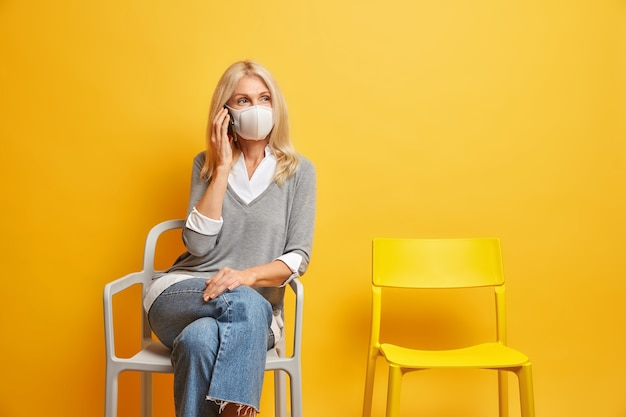 Social distancing concept. serious middle aged woman has telephone conversation via mobile phone poses near waiting room on chair with no people around wears protective face mask during epidemic