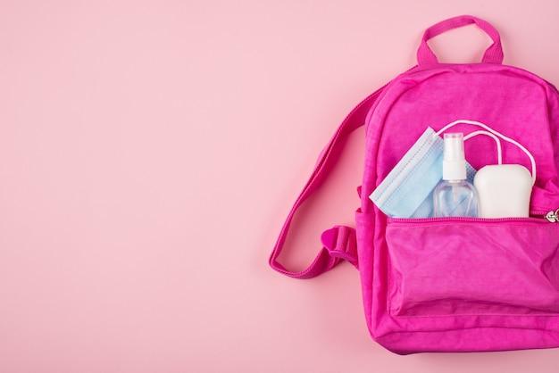 Концепция социального дистанцирования. фото розового рюкзака с синей маской, дезинфицирующее средство для рук, изолированное на пастельно-розовом фоне с copyspace