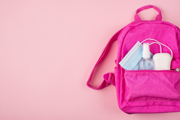 Social distancing concept. top above overhead view photo of pink backpack blue mask soap hand sanitizer isolated on pastel pink background with copyspace