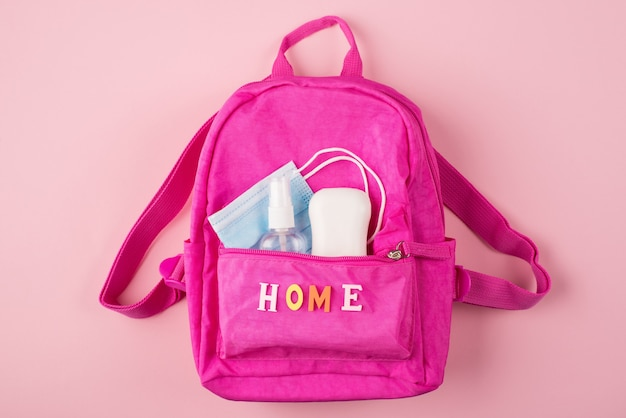 Social distancing concept. top above overhead view photo of pink backpack mask soap and sanitizer isolated on pastel pink background