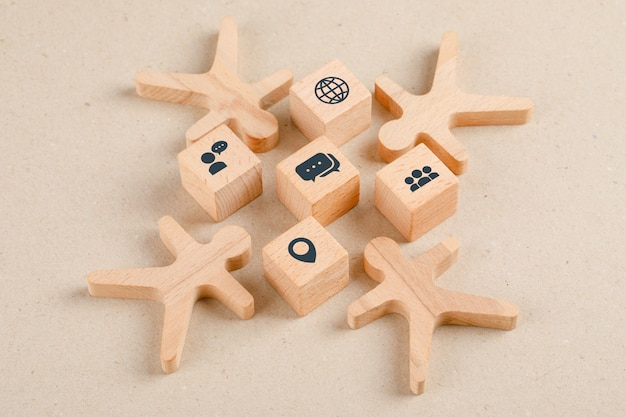 Social distancing concept with icons on wooden cubes, wooden figures high angle view.