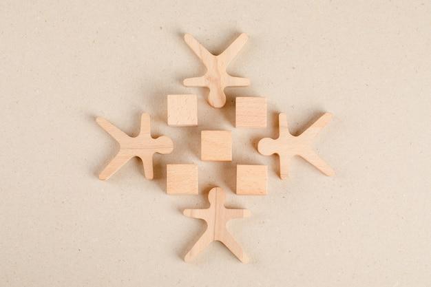 Социальная дистанцирование концепции с деревянными кубами и человеческими фигурами плоской планировки.