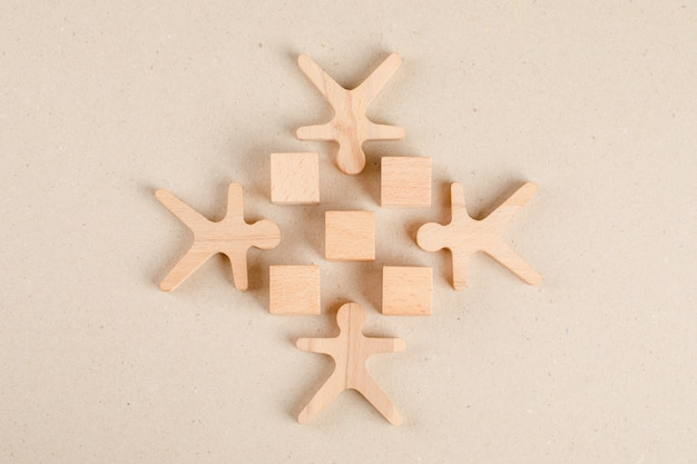 Social distancing concept with wooden cubes and human figures flat lay.