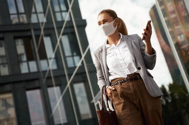 携帯電話を保持している間保護フェイスマスクを身に着けている社会的な距離の自信を持ってビジネス女性