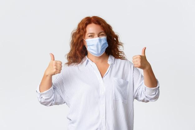 Социальное дистанцирование, меры профилактики коронавируса и концепция людей. оптимистичная улыбающаяся рыжая женщина средних лет в медицинской маске, показывает палец вверх, советует использовать защиту от вируса.