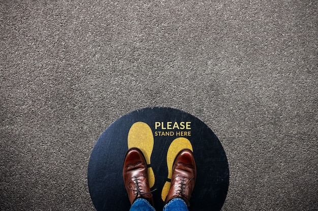 Social distancing for covid-19 situation concept. signage for cooperate in public place on the floor.