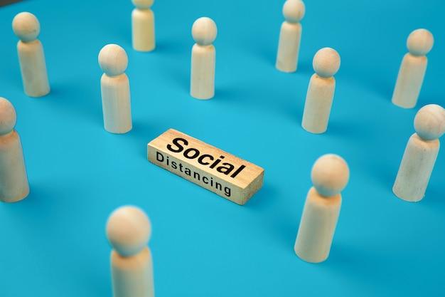 Социальное дистанцирование для коронавируса (covid-19) на деревянном игрушечном блоке.
