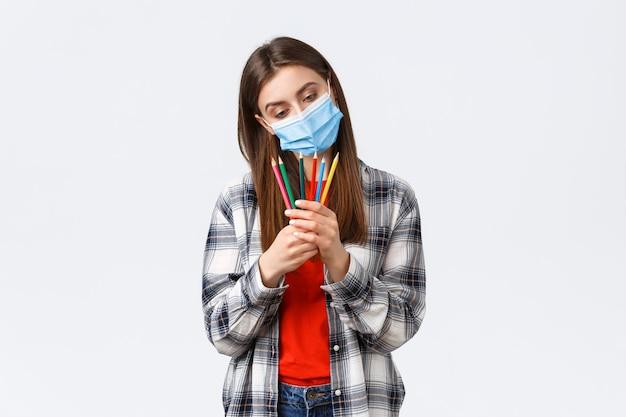 Covid-19の発生、コロナウイルスの概念に関する社会的距離、余暇、趣味。医療用マスクを身に着けた思いやりのあるキュートで夢のような女性が、どの色鉛筆を選ぶかを決め、何を描くかを考えます