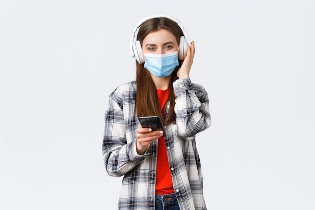 Covid-19の発生、コロナウイルスの概念に関する社会的距離、余暇、ライフスタイル。医療マスクで陽気な笑顔の女性、プレイリストのスマートフォンから曲を選んで、ワイヤレスヘッドフォンで音楽を聴きます。