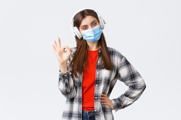 Covid-19の発生、コロナウイルスの概念に関する社会的距離、余暇、ライフスタイル。医療用マスクとヘッドホンを着用し、音楽を聴き、大丈夫なサインを見せ、承認するなど、かっこいい女性を喜ばせます。