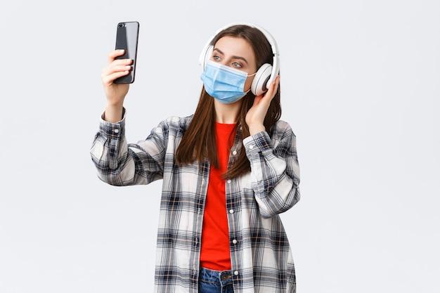 Covid-19の発生、コロナウイルスの概念に関する社会的距離、余暇、ライフスタイル。ヘッドフォンと医療マスクの女性が音楽を聴き、フィルターを使用して携帯電話で自分撮りをします。