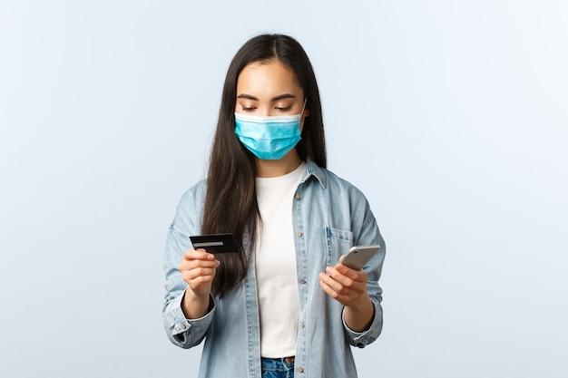 사회적 거리두기 생활 방식, covid-19 전염병 및 비접촉 쇼핑 개념. 모바일 애플리케이션에서 주문하는 동안 신용카드를 보고 있는 의료용 마스크를 쓴 매력적인 세련된 아시아 소녀