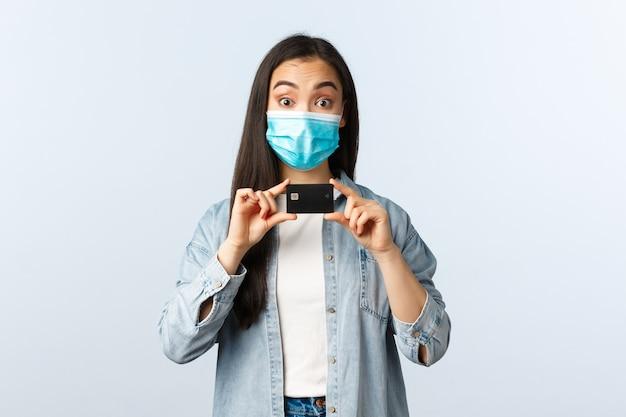 Социальное дистанцирование образа жизни, пандемия covid-19 и концепция бесконтактных покупок. жизнерадостная азиатская девушка в медицинской маске рекомендует использовать кредитную карту, открыть банковский счет или внести депозит