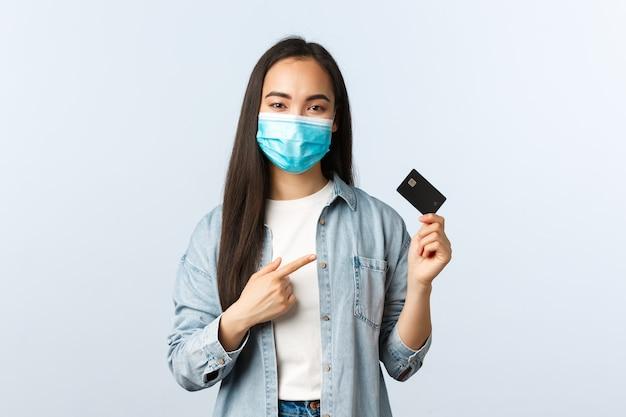 社会的距離を置くライフスタイル、covid-19パンデミックおよび非接触型ショッピングのコンセプト。クレジットカードを指す医療マスクの陽気なかわいいアジアの女性、アドバイスはオンラインで支払う、自宅から注文する