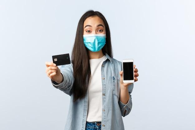 사회적 거리두기 생활 방식, covid-19 전염병 및 비접촉 쇼핑 개념. 온라인 주문 결제를 위해 신용카드를 사용하여 의료 마스크 조언을 하는 쾌활한 예쁜 아시아 소녀