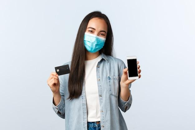 사회적 거리두기 생활 방식, covid-19 전염병 및 비접촉 쇼핑 개념. 스마트폰 화면과 신용카드를 보여주는 의료용 마스크를 쓴 쾌활한 아시아 여성, 인터넷 주문