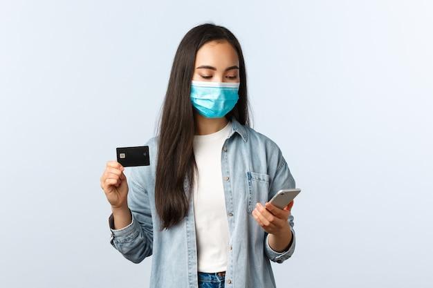 사회적 거리두기 생활 방식, covid-19 전염병 및 비접촉 쇼핑 개념. 의료용 마스크를 쓴 귀여운 10대 아시아 소녀, 신용카드를 보여주고 주문하는 동안 휴대전화를 쳐다본다