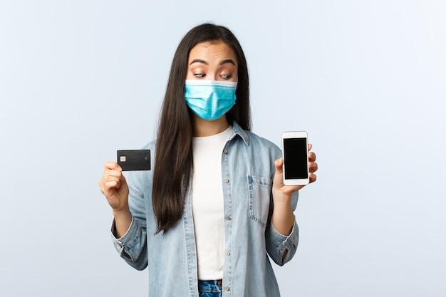 사회적 거리두기 생활 방식, covid-19 전염병 및 비접촉 쇼핑 개념. 의료용 마스크를 쓴 흥미진진한 아시아 소녀가 스마트폰 화면을 들여다보며 신용카드를 보여주고 있다
