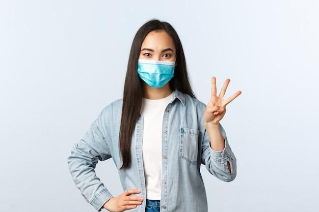 사회적 거리를 두는 생활 방식, covid-19 전염병 및 사람들의 감정 개념. 의료 마스크를 쓴 흥분한 귀여운 아시아 여성은 3개의 평화를 주문하고, 손가락으로 숫자를 표시하고, 흰색 배경을 보여줍니다.