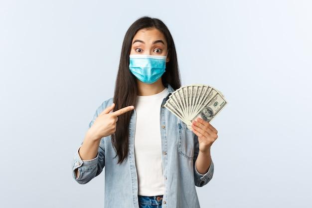 Социальное дистанцирование образа жизни, концепция бизнеса и занятости пандемии covid-19. взволнованная азиатская сотрудница предлагает вам заработать много денег, указывая на наличные доллары, надев медицинскую маску