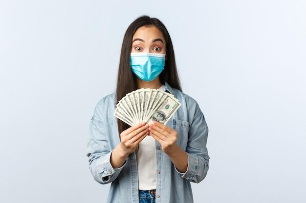 사회적 거리를 두는 생활 방식, covid-19 전염병 비즈니스 및 고용 개념. 의료용 마스크를 쓴 흥분한 아시아 여성은 집에서 돈을 들고 온라인 작업에 대한 대가를 받았습니다.