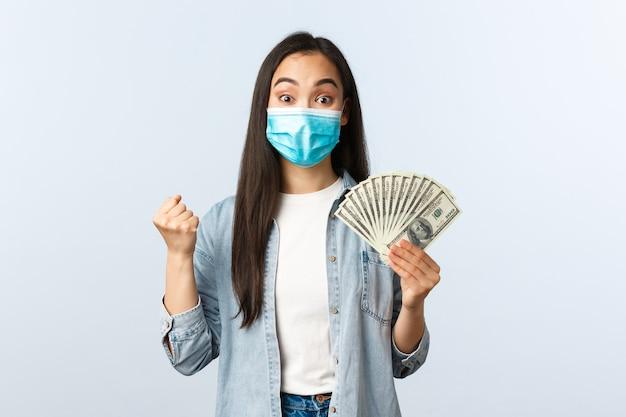 사회적 거리를 두는 생활 방식, covid-19 전염병 비즈니스 및 고용 개념. 복권에 당첨된 행복한 아시아 여성, 의료용 마스크를 쓰고 기뻐하고, 돈을 보여주고, 현금을 들고