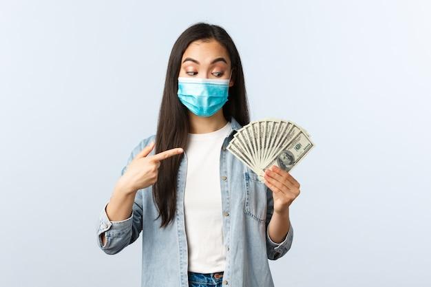사회적 거리를 두는 생활 방식, covid-19 전염병 비즈니스 및 고용 개념. 의료용 마스크를 쓴 흥분한 아시아 소녀가 현금을 가리키며 큰 돈을 발견했다
