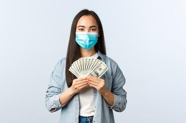Социальное дистанцирование образа жизни, концепция бизнеса и занятости пандемии covid-19. довольная жизнерадостная азиатская сотрудница в медицинской маске зарабатывает деньги, показывая наличные, работая из дома