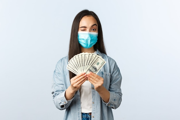 사회적 거리를 두는 생활 방식, covid-19 전염병 비즈니스 및 고용 개념. 의료 마스크 윙크에서 성공적인 여성 프리랜서를 기쁘게 하고, 구직 사이트에 가입하도록 장려하고, 돈을 보여줍니다.