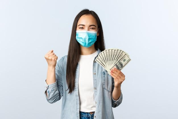 사회적 거리를 두는 생활 방식, covid-19 전염병 비즈니스 및 고용 개념. 기뻐하는 아시아 여성은 급여를 받고, 의료 마스크를 쓰고, 주먹을 휘두르고, 돈을 보여주고, 월급날에 승리합니다.