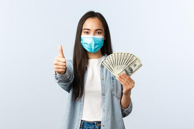 사회적 거리를 두는 생활 방식, covid-19 전염병 비즈니스 및 고용 개념. 의료용 마스크를 쓴 만족스러운 귀여운 아시아 여성은 엄지손가락과 현금을 보여주고, 돈을 벌기 위해 좋은 직업을 추천합니다